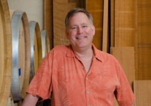 Tom by the wine barrels, wood in the background; photo by Tim Celeski